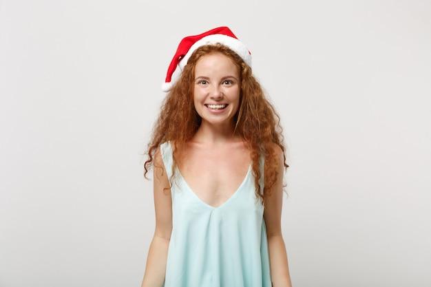 Belle jeune fille de santa rousse dans des vêtements légers, chapeau de noël isolé sur fond blanc, portrait en studio. concept de vacances de célébration de bonne année 2020. maquette de l'espace de copie. regarder la caméra.