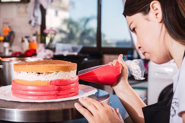 Belle jeune fille se concentrant et décorant un gâteau - jeune boulanger en tablier travaille dans la cuisine.