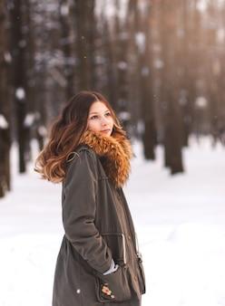 Belle jeune fille se promène dans le parc en hiver par une journée ensoleillée