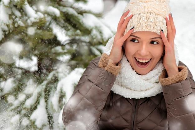 Une belle jeune fille se réjouit de la neige de l'hiver dans le parc parmi les sapins dans un chapeau et une écharpe gros plan.