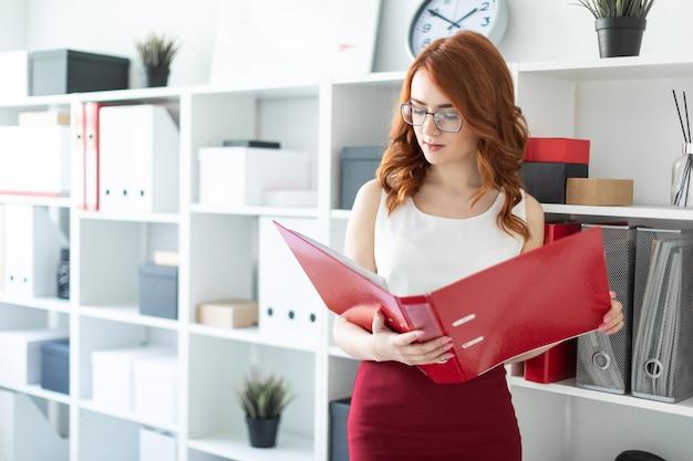 Une belle jeune fille se tient près d'une pile dans le bureau et tient un dossier avec des documents à la main.