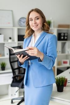 Une belle jeune fille se tient près d'une table dans le bureau et tient un livre ouvert dans ses mains.