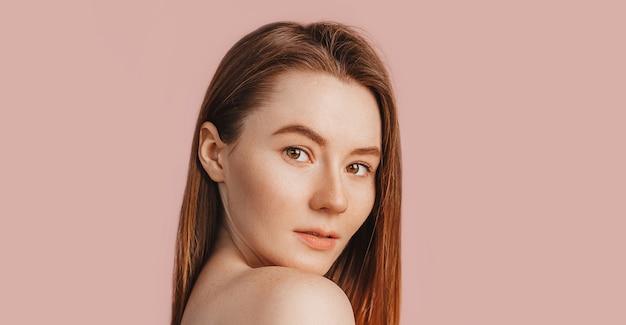 Belle jeune fille sensuelle avec une peau propre sur un espace rose avec une maquette