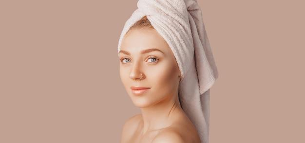 Belle jeune fille sensuelle à la peau propre sur fond beige avec une maquette. femme seins nus dans une serviette. le concept des cures thermales, beauté et soins naturels, jeunesse, crème et masque, fraîcheur