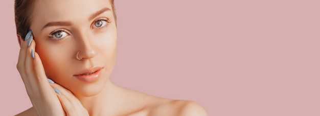 Belle jeune fille sensuelle avec une peau propre sur fond rose avec une maquette. femme seins nus dans une serviette. le concept des cures thermales, beauté et soins naturels, jeunesse, crème et masque, fraîcheur