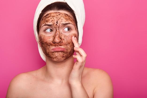 Belle jeune fille avec une serviette blanche sur la tête. charmante femme applique scrab cosmétique. traitements esthétiques à domicile. soin quotidien de la peau
