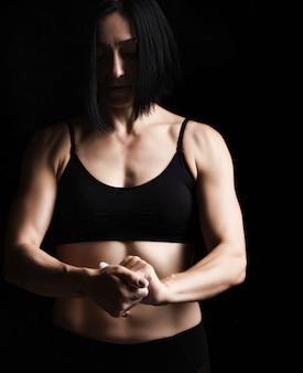 Belle jeune fille avec une silhouette sportive vêtue d'un haut noir frappe dans ses mains avec de la magnésie blanche