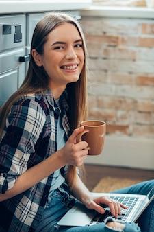 Belle jeune fille souriante et buvant du thé assise avec un gadget à la maison