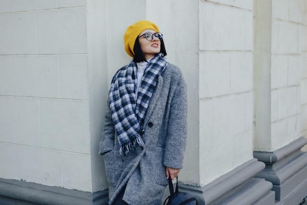 Belle jeune fille souriante à lunettes en manteau et béret jaune sur un fond clair simple