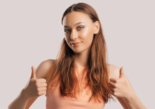 Belle jeune fille souriante et montre le geste du pouce vers le haut avec les deux mains sur un fond blanc isolé. la femme positive indique une idée, un endroit pour la publicité