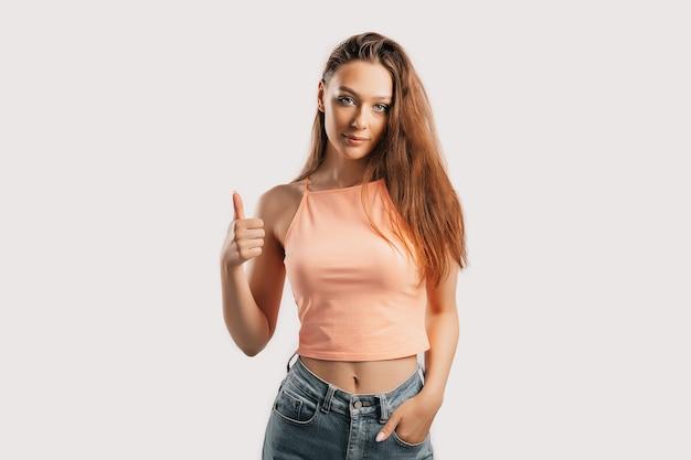 Belle jeune fille souriante et montre les pouces vers le haut la main de geste sur un fond blanc isolé. la femme positive indique une idée, un endroit pour la publicité