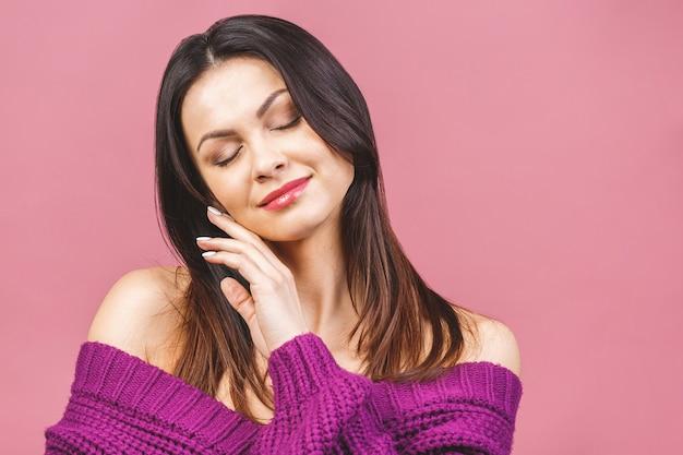 Belle jeune fille souriante avec une peau propre, un maquillage naturel et des dents blanches sur fond rose.