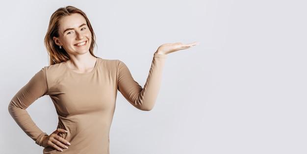 Belle jeune fille souriante et pointant sa main sur le côté sur un fond blanc isolé