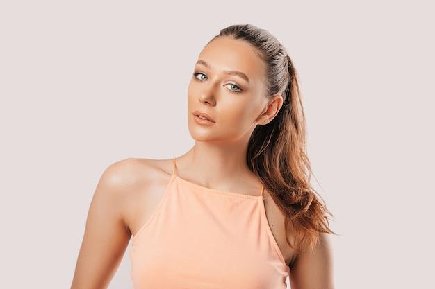 Belle jeune fille souriante et posant en regardant la caméra sur un fond blanc isolé. femme brune positive. regard gentil. beau visage.