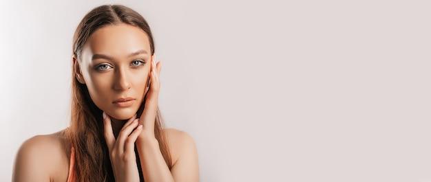 Belle jeune fille souriante et posant en regardant la caméra sur un fond blanc isolé avec maquette. femme brune positive. regard gentil. beau visage