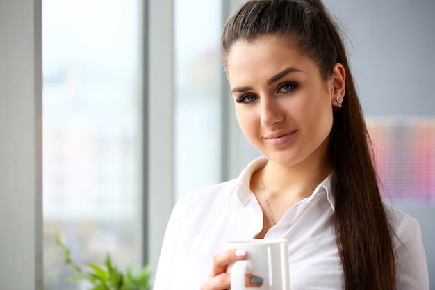 Belle jeune fille souriante tenir dans les bras portrait de grande tasse