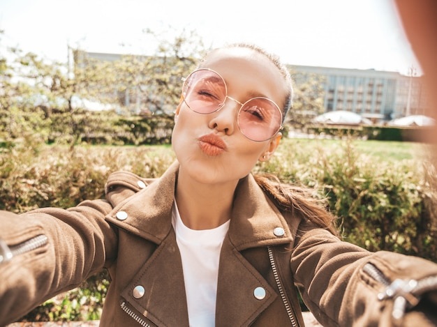 Belle jeune fille souriante en veste d'été hipster et jeans modèle prenant selfie sur smartphone