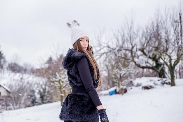 Une belle jeune fille souriante en vêtements noirs et un bonnet tricoté blanc en hiver