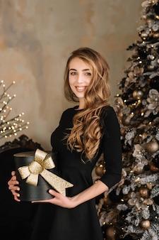 Belle jeune fille sourit et tient la boîte-cadeau dans les mains
