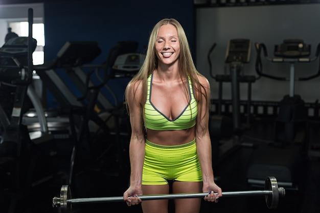 Belle jeune fille sportive athlétique, fille de remise en forme s'entraîne dans la salle de gym, faire des exercices avec une barre