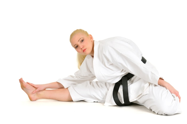 Belle jeune fille sportive de karaté blonde dans un kimono fait une position pour commencer l'entraînement