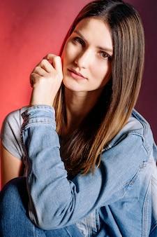 Belle jeune fille en studio sur fond rouge. portrait de gros plan. coiffure. cheveux et peau lisses et brillants. mode, beauté, maquillage, cosmétiques, salon de beauté, style.
