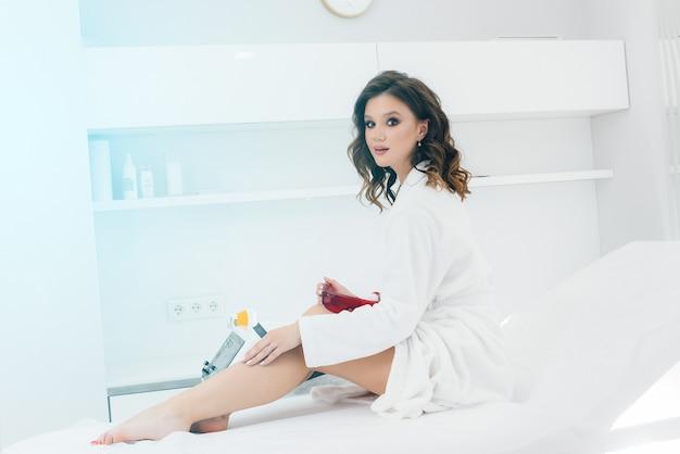 Une belle jeune fille subira une épilation au laser avec un équipement moderne dans un salon spa. salon de beauté. soin du corps.