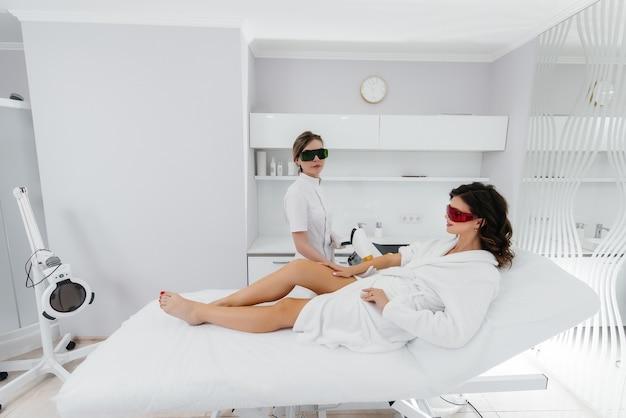 Une belle jeune fille subira une épilation au laser avec un équipement moderne dans un salon de spa. salon de beauté. soin du corps.