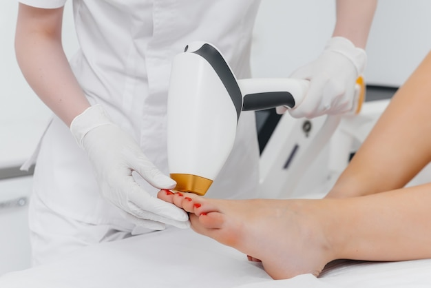 Une belle jeune fille subira une épilation au laser avec un équipement moderne dans un salon de spa