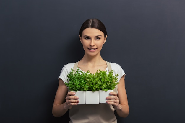 Belle jeune fille en tablier tient des plantes.