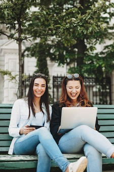 Belle jeune fille de taille plus aux cheveux rouges en riant en regardant son ordinateur portable près de sa petite amie brune qui regarde la caméra en riant sur un banc.