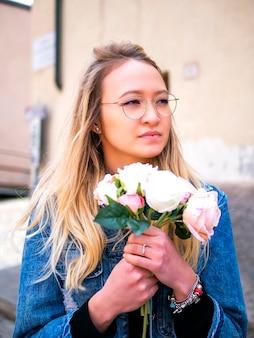 Belle jeune fille tartare à lunettes avec un bouquet de fleurs.