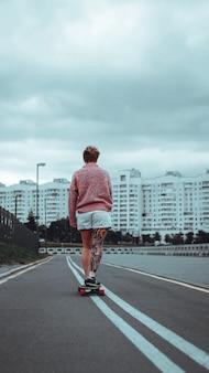 Belle jeune fille tatouée avec longboard dans la ville. elle a un tatouage traditionnel japonais