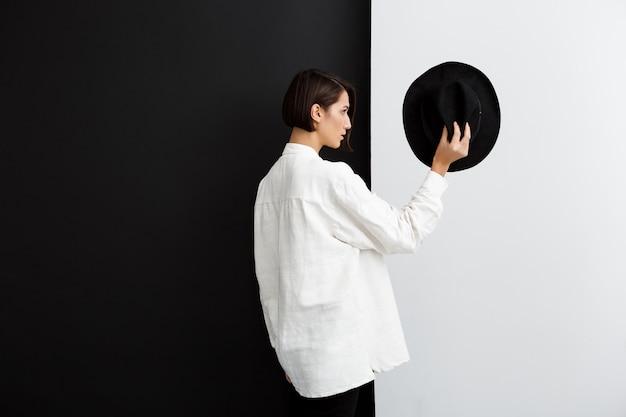 Belle jeune fille tenant un chapeau sur un mur noir et blanc