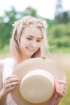 Belle jeune fille tenant un chapeau avec une sauterelle verte