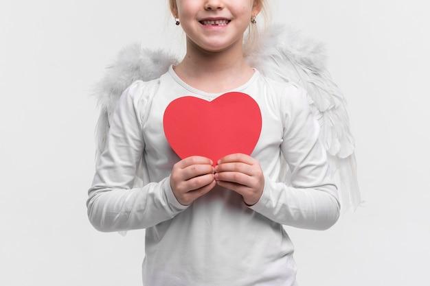 Belle jeune fille tenant un coeur