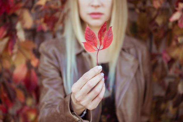 Belle jeune fille tenant une feuille rouge