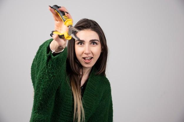 Une belle jeune fille tenant des pinces dans ses mains.