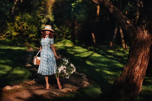 Belle jeune fille tendre dans un chapeau de paille avec un bouquet de fleurs. charmante demoiselle au bouquet de lilas. lilas. belle fille dans une robe lilas.