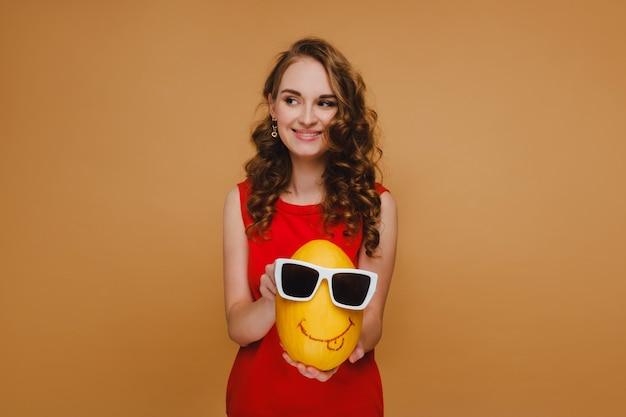 Belle jeune fille tient le melon de mains. le melon porte des lunettes et une émoticône est dessinée. fille en robe rouge