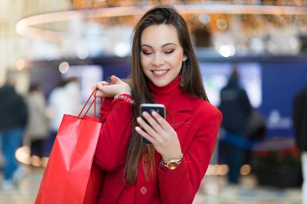 Belle jeune fille touristique à milan shopping à milan en utilisant un smartphone