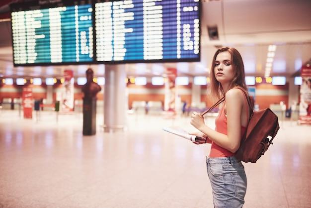 Belle jeune fille touristique avec sac à dos à l'aéroport international, près du panneau d'information de vol.