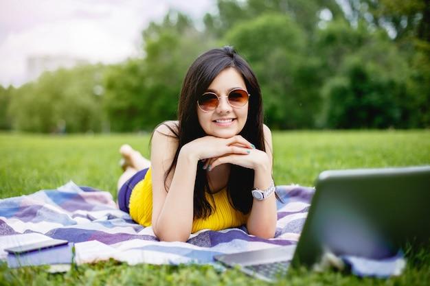 Belle jeune fille travaillant sur un ordinateur portable à l'extérieur