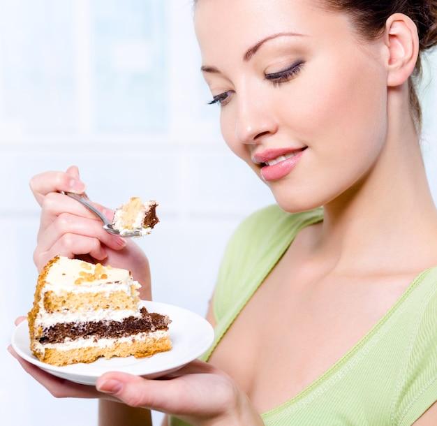 Belle jeune fille va manger un gâteau sucré
