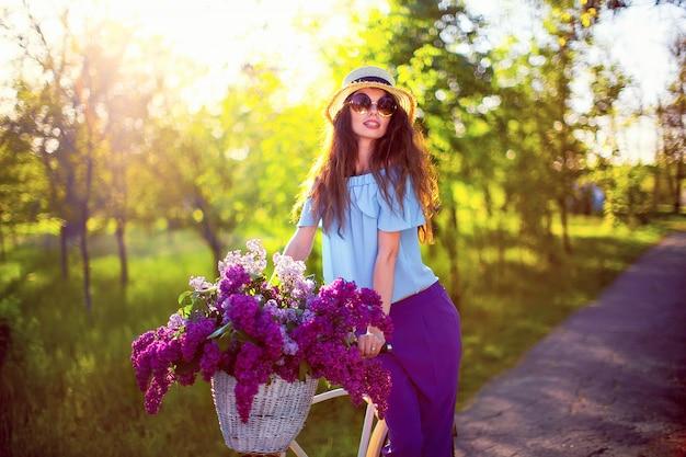 Belle jeune fille à vélo vintage et des fleurs sur la ville de backgroundd à la lumière du soleil en plein air.