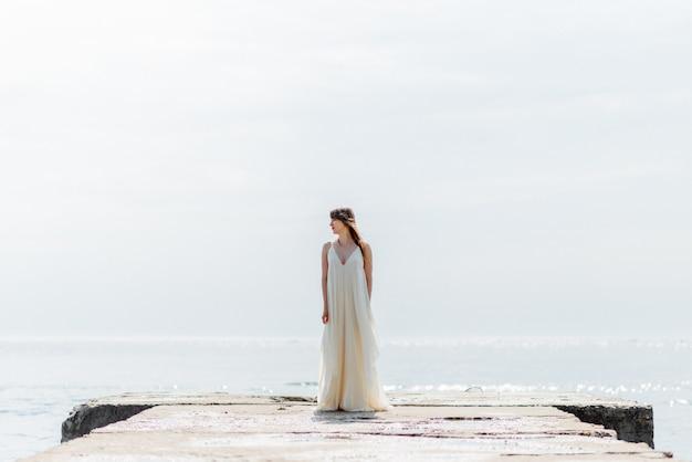 Une belle jeune fille vêtue d'une longue robe blanche se promène le long de la plage et de la jetée contre la mer.