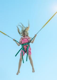 Une belle jeune fille vêtue d'une robe aux cheveux flottant saute sur l'attraction. la balade revigorante.
