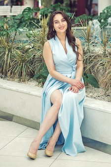 Belle jeune fille vêtue d'une robe bleu clair, talons hauts beiges assis dans la rue.