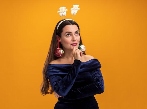 Belle jeune fille vêtue d'une robe bleue et cerceau de cheveux de noël tenant des boules de noël sur les oreilles - isolé sur fond orange