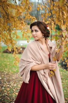 Belle jeune fille vêtue d'une robe rouge dans la forêt d'automne